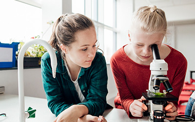 Two girls in a school lab, one is looking into a microscope.