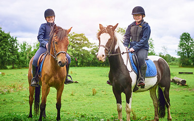 Photo of two girls on horseback.